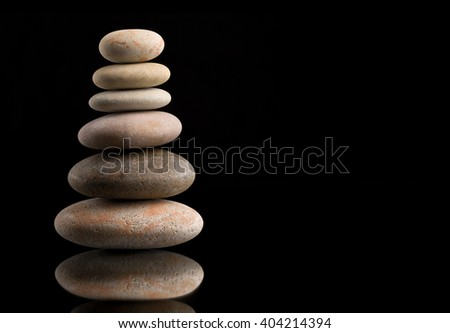 Pile of balancing pebble stones, like ZEN stone, on black background, spa tranquil scene concept with reflection - stock photo
