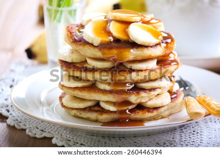 Pile of banana pancakes with caramel drizzle over and cup of tea - stock photo