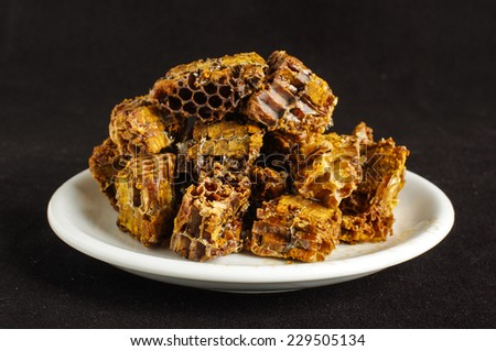 Pile of bee pollen or bee bread on the black background - stock photo