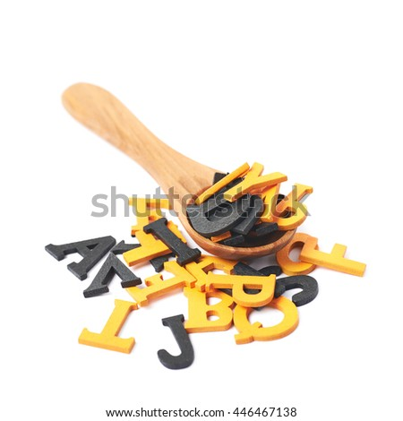 Pile of black and orange painted wooden letters with the wooden serving spoon over it, composition isolated over the white background - stock photo