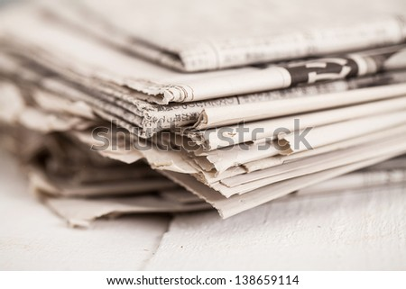 Pile of black and white newspapers on a wooden table - stock photo