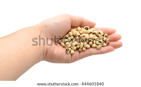 pile of black eyed beans in a hand on white background
