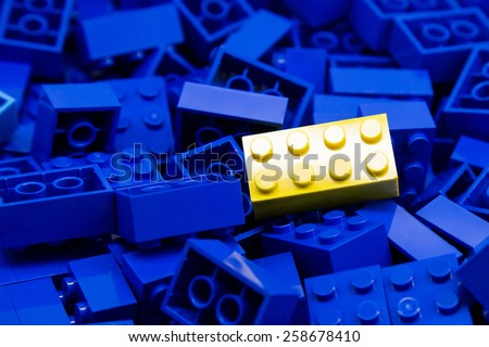 Pile of blue color building blocks with selective focus and highlight on one particular yellow block using available light. - stock photo