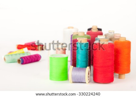 Pile of  bobbins of colorful threads - stock photo
