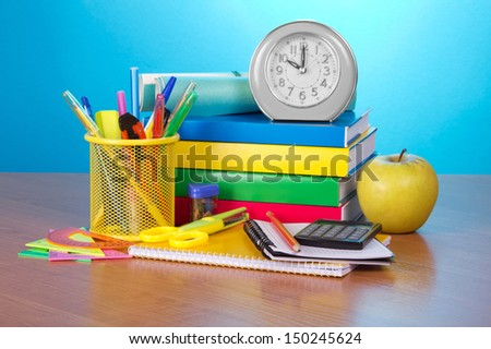 Pile of books, an exercise book, office supply, the calculator, an alarm clock and apple on a table