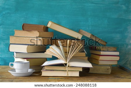 pile of books and a cup of coffee, free copy space - stock photo