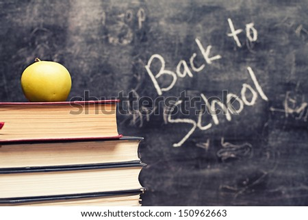 pile of books and a green apple in front of a blackboard