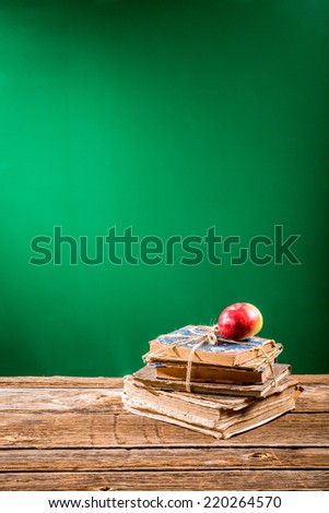 Pile of books and apple to blackboard background - stock photo