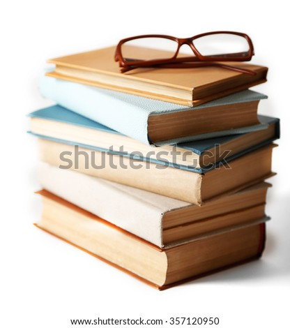 Pile of books and eyeglasses on it isolated on white background - stock photo