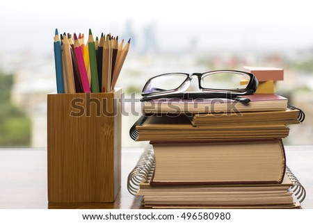 Pile of books and notepads, glasses, stickers and pencils in wooden box on blurry background. Education concept