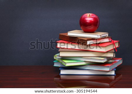 Pile of books and red apple on the desk over the blackboard - stock photo