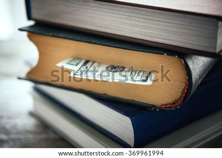 Pile of books and us dollar bill - stock photo