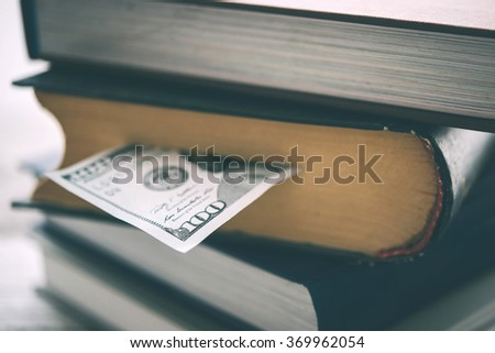 Pile of books and us dollar bill. Toned picture