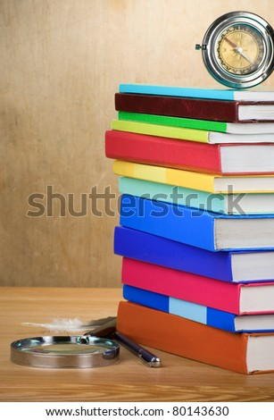 pile of books, magnifier and compass with feather on wooden background