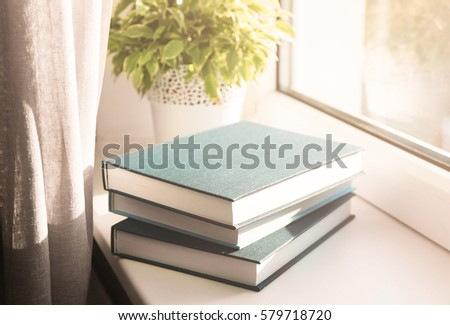 Pile of books on windowsill