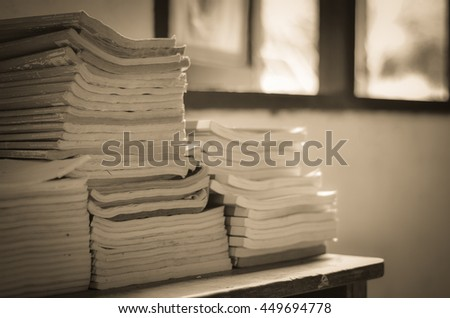 pile of books on wood table edge window in the classroom. - stock photo