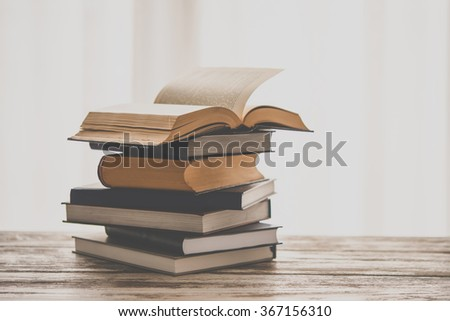 Pile of books on wooden table. Education and reading concept. Toned picture - stock photo