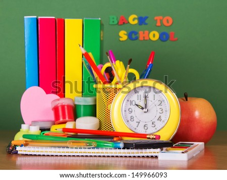 Pile of books, set of writing-materials an alarm clock and apple on a green background