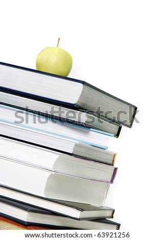 pile of books with apple on top over white