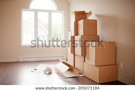 Pile of boxes being opened after moving. Short depth of field in natural light. - stock photo