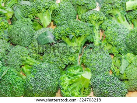 Pile of branches of fresh broccoli laid out on a wooden surface