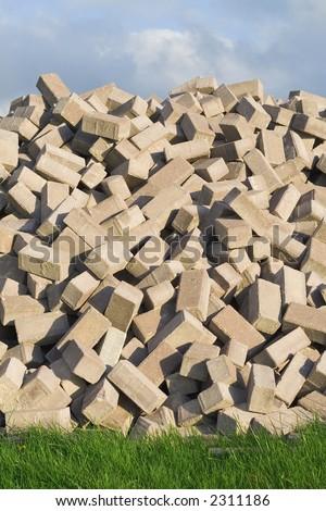 Pile of bricks between grass and sky. - stock photo