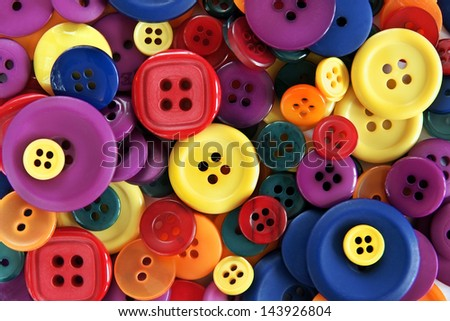 Pile of brightly colored buttons used in sewing and haberdashery - stock photo