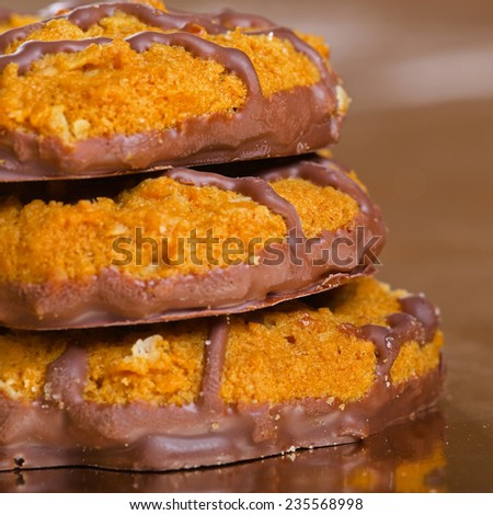Pile of brown, chocolate cookies on on yellow glossy paper with reflection, closeup
