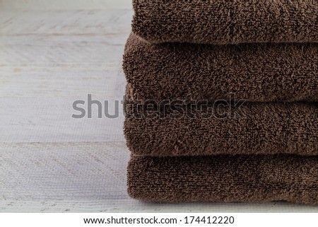 Pile of brown, organic cotton towels. - stock photo