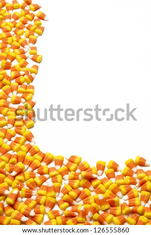 Pile of candy corn scattered on white floor. - stock photo