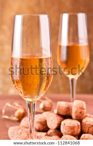 Pile of champagne corks with two glasses of champagne at the background - stock photo