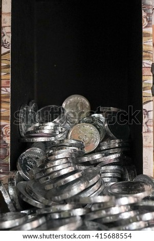 Pile of chocolate coins wrapped in shiny silver tinfoil, pouring from treasure box. Pirate treasure / finance concept. Empty space on top for text, copy space. Selective focus