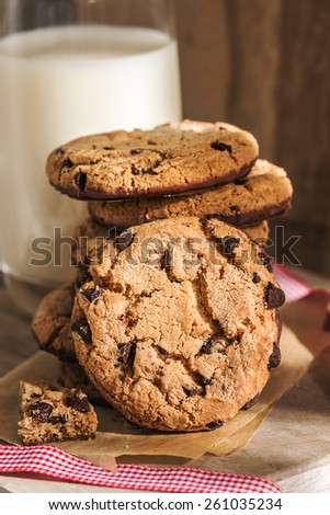 Pile of chocolate cookies with a glass of milk - stock photo