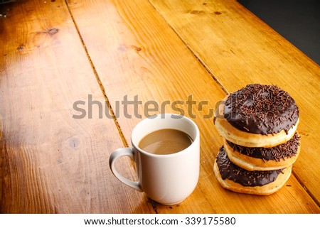 pile of chocolate doughnuts with a hot drink in wood background - stock photo