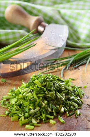 Pile of chopped fresh chives lying on a wooden kitchen table with a curved chopping knife and checked green and white cloth - stock photo