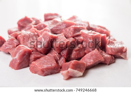 Pile of chopped raw beef steak on the white marble background table.