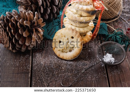 Pile of Christmas fruit mince pies and pine cones over rustic wooden background  - stock photo
