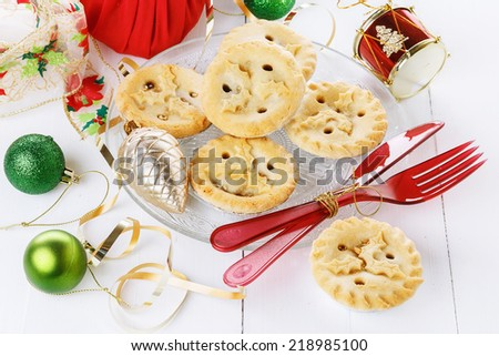 Pile of Christmas fruit mince pies, Christmas decorations over white wooden background - stock photo