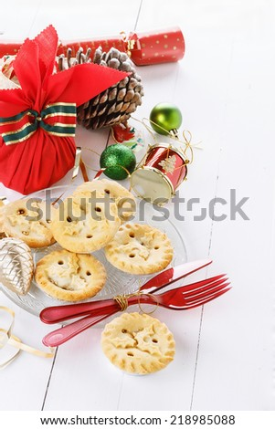 Pile of Christmas fruit mince pies, Christmas treats and decorations over white wooden background - stock photo