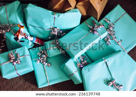 Pile of Christmas gifts on floor wrapped in turquoise gift wrap - stock photo