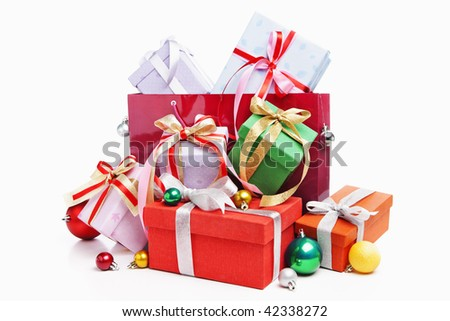 Pile of Christmas present with shopping bag, shot against white background - stock photo