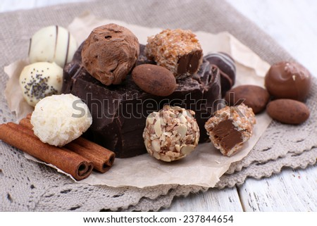Pile of chunk of chocolate and truffles with cinnamon stick on crumbled paper, grey material and wooden background - stock photo