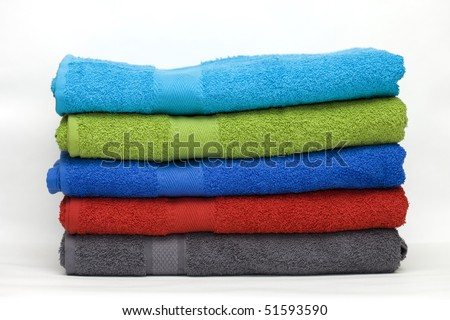 Pile of clean terry towels of different colors on a white background