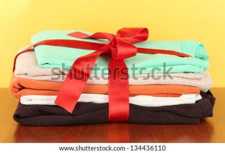 Pile of clothing with red ribbon and bow on table on yellow background - stock photo