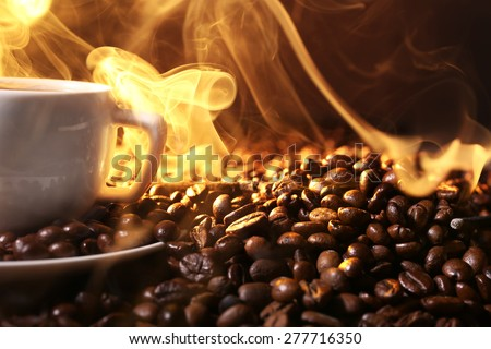 Pile of coffee beans and cup of hot coffee in beam on dark background