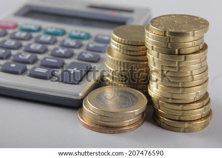 Pile of coins and calculator - stock photo