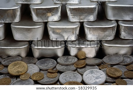 Pile of coins from around the world and bars of silver - stock photo
