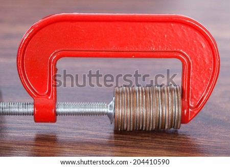 Pile of coins in clamp on desk - stock photo