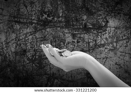 pile of coins in hand with scratched steel plate background ,black and white tone