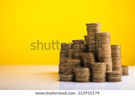Pile of coins money on yellow background - stock photo